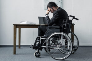 Depressed disabled businessman sitting in wheelchair at workplace with bowed head
